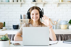 Girl waving at computer while taking an online class