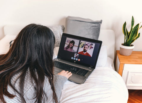 Woman video chatting friends while quarantining