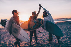 Surfers high fiving on the beach