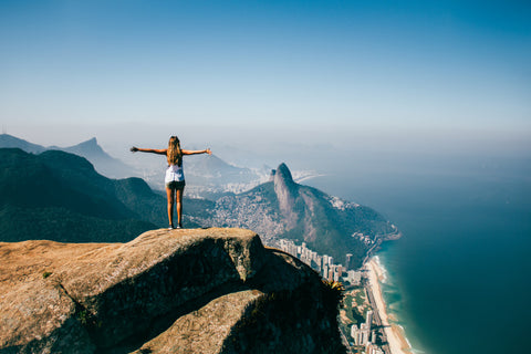 Woman standing on top of mountain with open arms