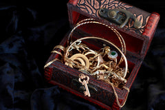 Brown treasure box filled with gold coins and necklaces