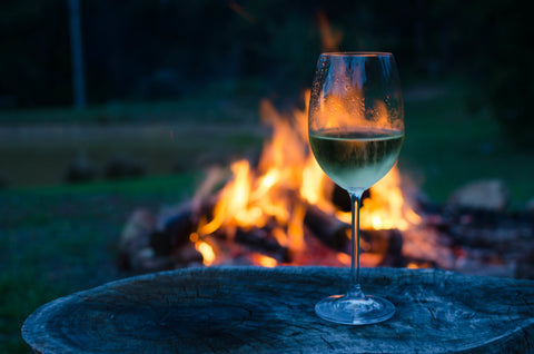 Glass of wine on a log in front of camp fire