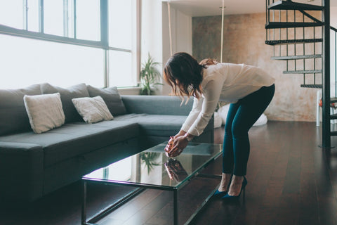 Woman decorating placing object on coffee table in home