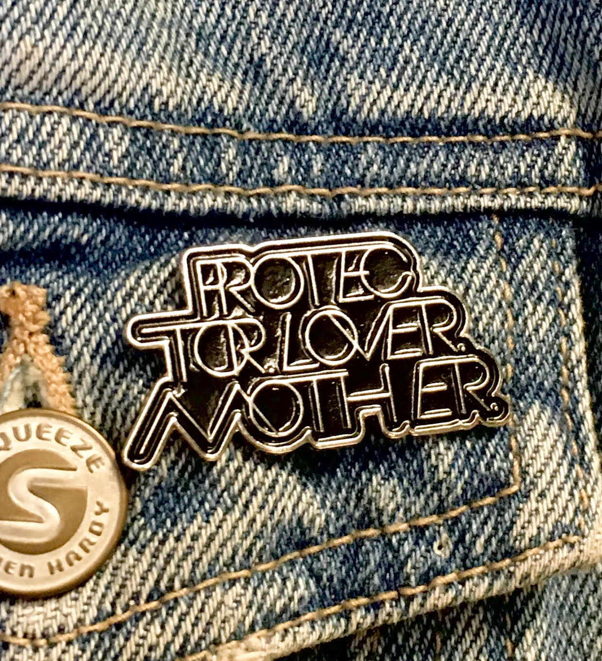 INTERLOCK PROTECTOR. LOVER. MOTHER.® SOFT ENAMEL PIN - SILVER & BLACK
