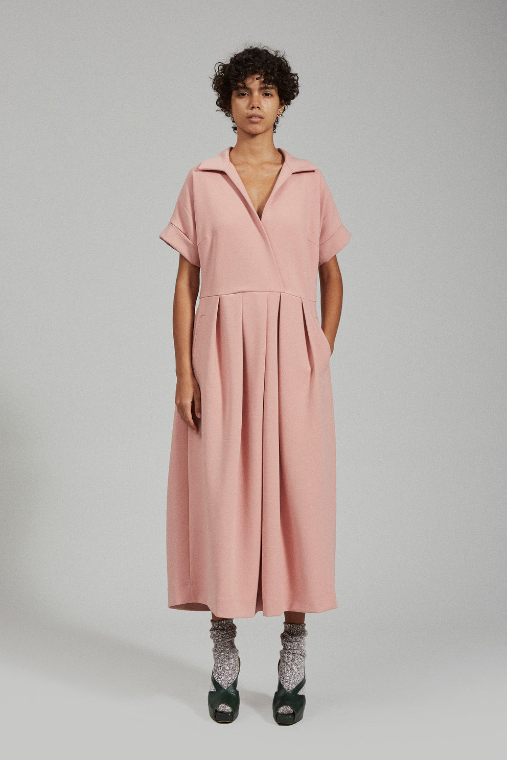 """Samya is 5'9.5"""" (176 cm) and wears a size 4 A sister to the Ardent Jumpsuit, the Tempo Dress is a waisted pleat front dress with midi length. It has a slightly loose, off the body fit which allows the pleats to move and for the whole style to drape around the neckline. Innsbruck is one of our favorite suiting fabrics; it holds structure while having enough stretch to provide flexibility and comfort."""