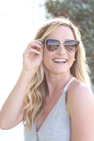 A woman outdoors wearing sunglasses and smiling at something off-camera.