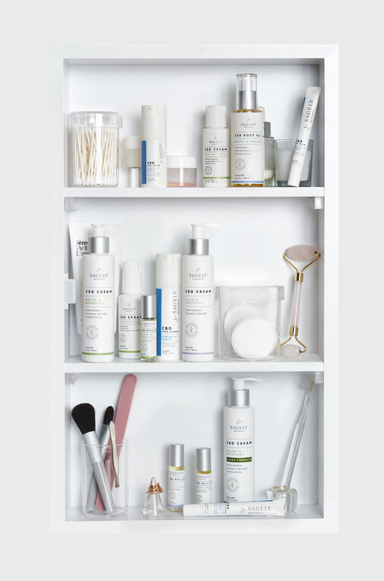 A medicine cabinet containing shelves with Sagely Naturals CBD cream, CBD capsules, CBD spray, CBD roll-ons, makeup brushes, makeup pads, and cotton buds.