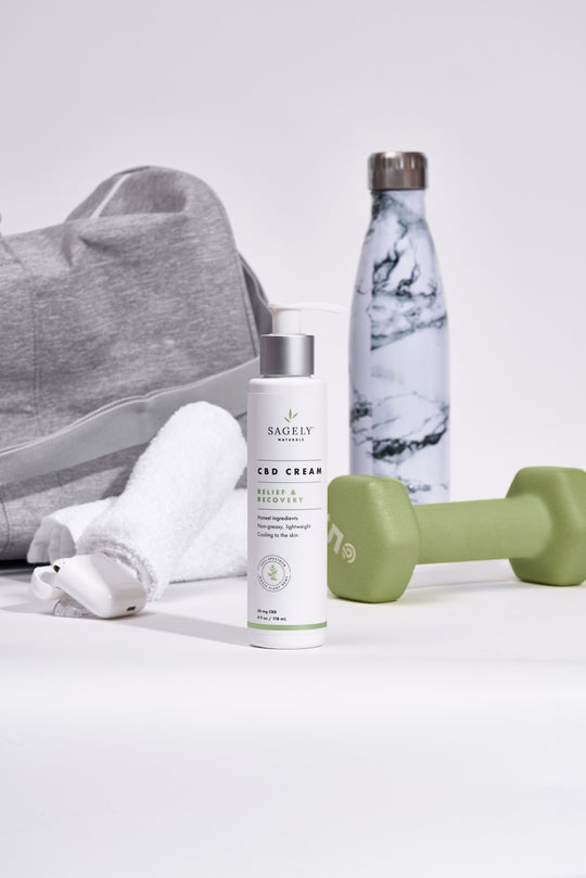 Sagely Naturals CBD Cream with gym bag, water bottle, towel and dumbell in background.