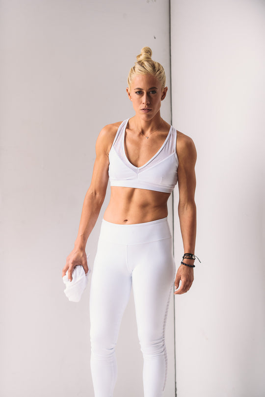 Lacey Stone in white workout clothes holding a white towel.
