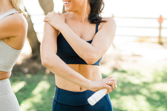 A woman in workout wear rubbing Sagely Naturals cream into her shoulder.