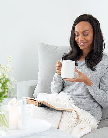 Sagely Naturals Calm & Centered Cream sitting on a table in front of woman drinking out of a white mug and reading a book.