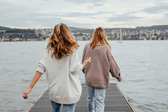 Two women walking on a pontoon toward the water's edge.
