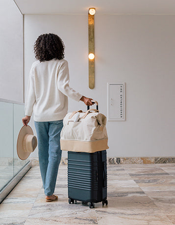 A woman rolling her suitcase and carry o, with Sagely Naturals CBD Cream, through a hotel