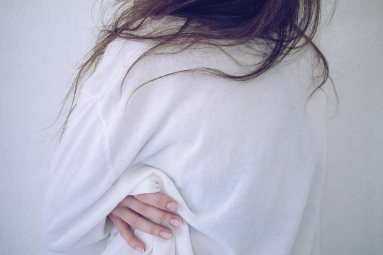 A photo of a woman in a white shirt holding her back and hips
