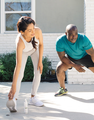 A woman and man in workout clothes stretching outside.
