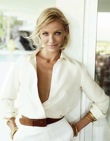 Cameron Diaz in a white pants suit standing by a white door frame.