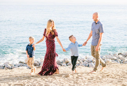 Nicole Neves walking on a beach with her two sons and husband