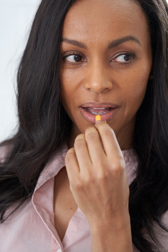 A woman with dark hair placing a Sagely Naturals capsule to her lips.