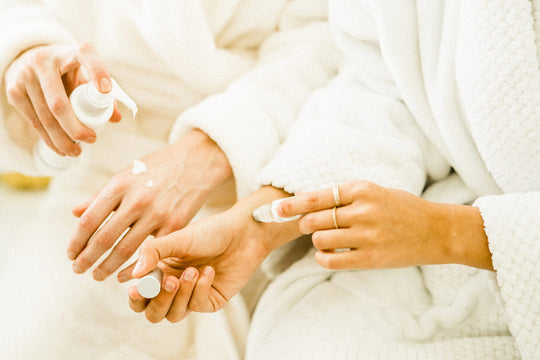 Sagely Naturals roll-on and creme being held by two models in white robes.
