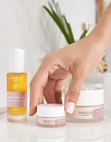 The Sagely Naturals Brightening CBD Skincare collection with a hand grabbing the Sagely Naturals Brightening CBD Eye Cream.