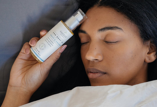Woman in bed holding her Sagely Naturals Drift & Dream CBD Body Oil