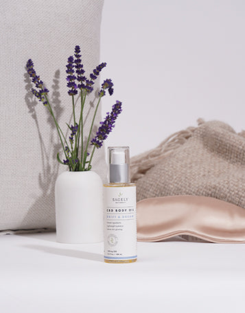 Sagely Naturals CBD Drift & Dream CBD Body Oil on bench in front of a lavender plant and eye mask.