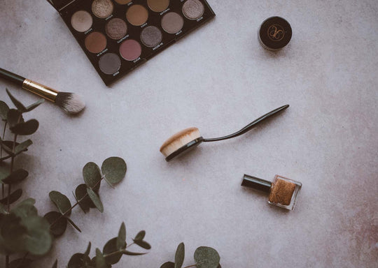 A photo of makeup brushes and makeup lying on a counter top with eucalyptus leaves