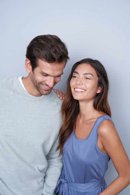 A woman with her hand on a man's shoulder who is leaning in laughing.