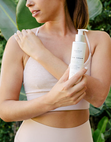 A woman wearing exercise clothing standing outside using Sagely Naturals Relief & Recovery CBD Cream on her shoulder.