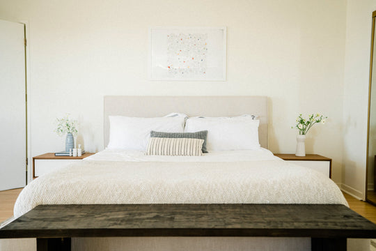A bed with crisp white sheets, pillows, framed picture above bed, and bedside tables with flowers and Sagely Naturals CBD products on the bedside table.