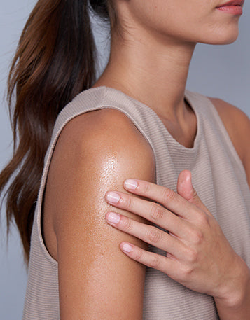 A woman with long dark hair wearing a singlet and putting CBD Spray on her shoulder.