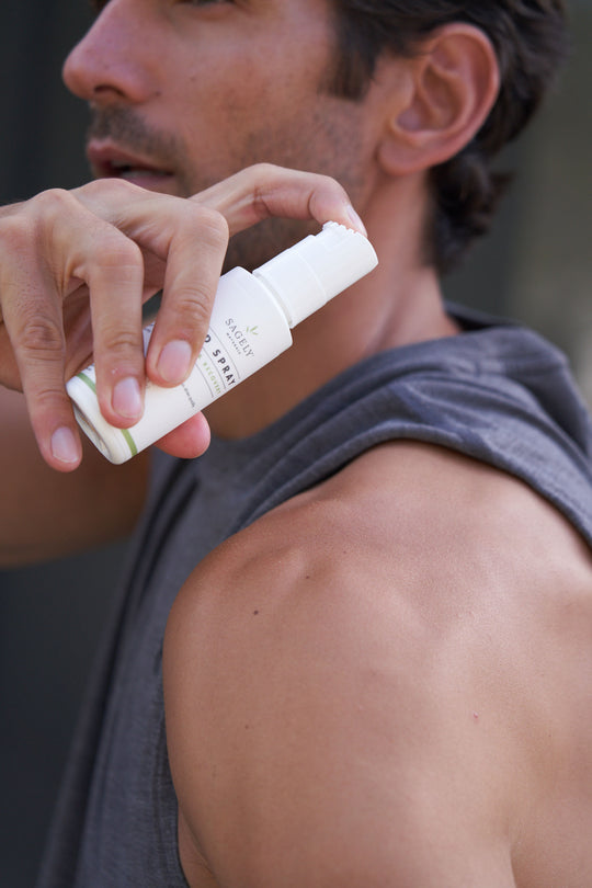 Marathon Runner using Sagely Naturals CBD Spray on his shoulder before working out