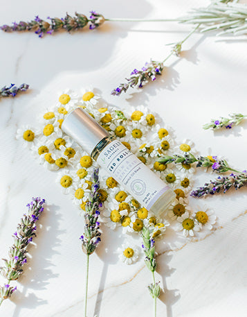 Sagely Naturals Calm & Centered CBD Roll-On lying among flowers.