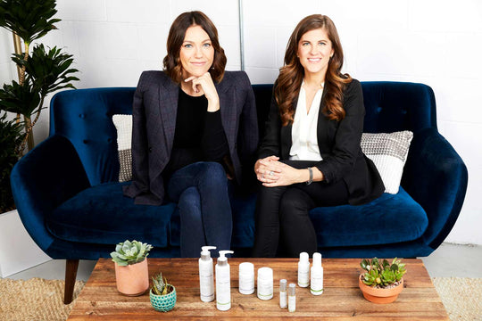 Sagely Naturals founders sitting on a blue couch & table with Sagely Naturals products displayed.