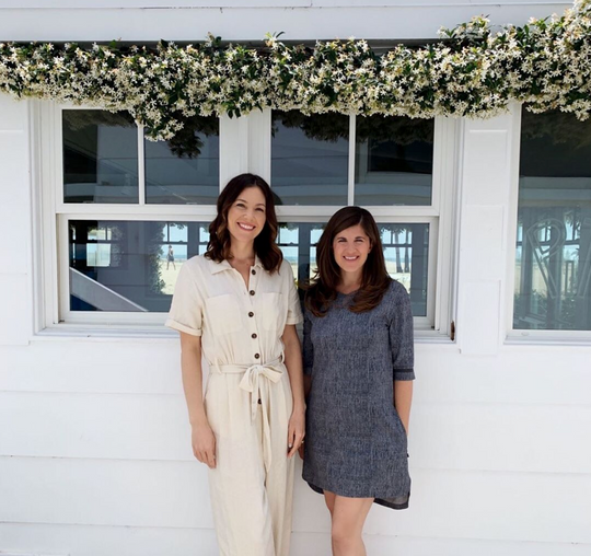 Sagely Naturals cofounders Kerrigan & Kaley standing outside in front of glass windows