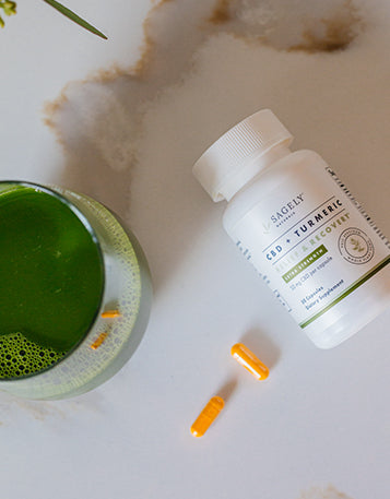 Sagely Naturals Relief & Recover CBD & Turmeric capsules next to a glass of green juice.