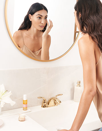 A woman standing in the bathroom looking at herself in the mirror as she applies the Sagely Naturals Brightening CBD Eye Cream.