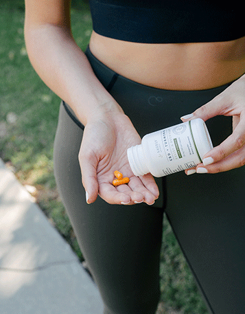 A woman in workout clothes pouring some Sagely Naturals Relief & Recovery CBD Capsules into her hand.