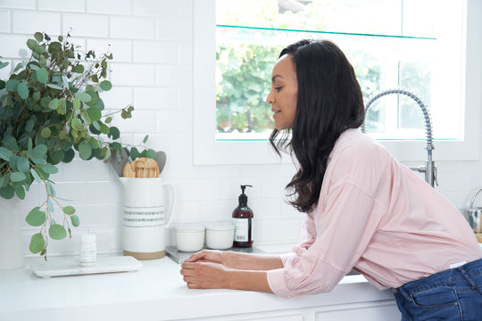 Woman in her kitchen with Sagely Naturals Relief & Recovery CBD Capsules