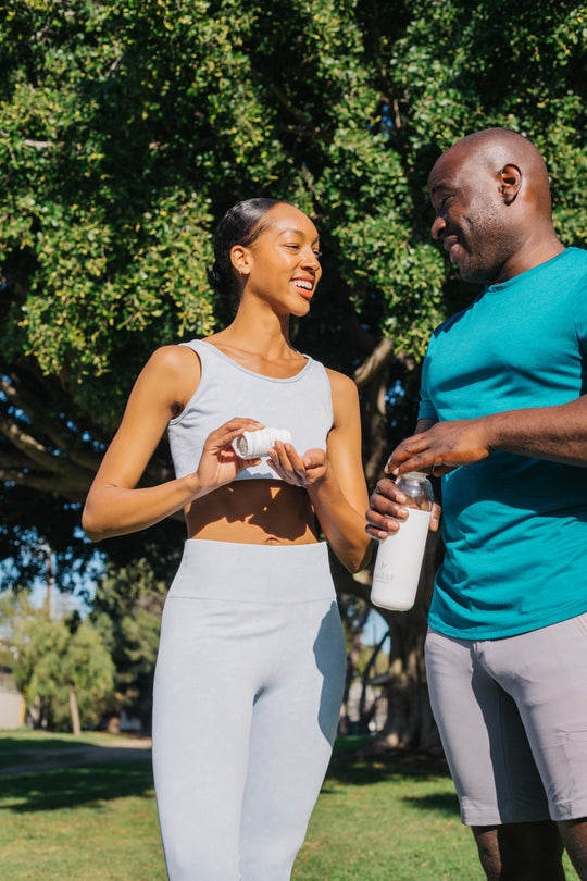 Man and woman exercising outdoors while drinking water and taking Sagely Naturals CBD capsules