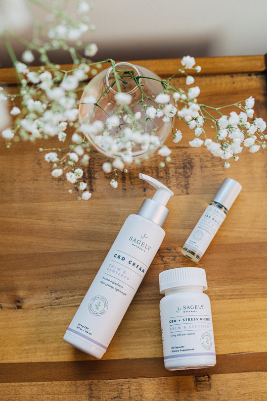 Sagely Naturals Calm & Centered CBD cream, CBD roll-on and CBD capsules on top of a wooden table, next to a vase of baby's breath.