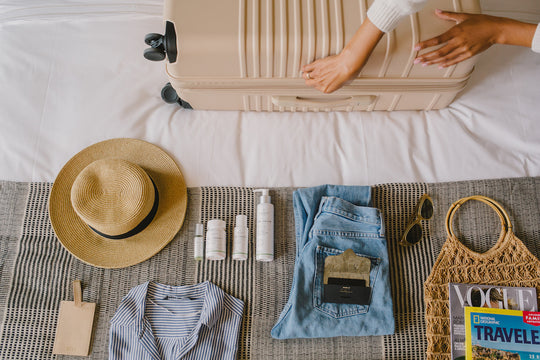Sagely Naturals products lying on bed next to suitcase, hat, sunglasses.