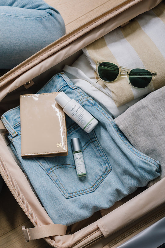 Open suitcase with a diary, sunglasses, clothing, and Sagely Naturals CBD cream and roll-on bottles.
