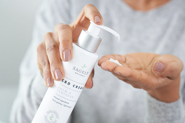 A close up image of a woman holding a bottle of Sagely Naturals Calm & Centered CBD Cream as she presses some out into her hand.