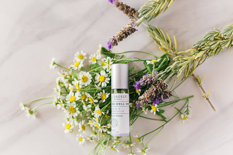 Sagely Naturals Calm & Centered CBD Roll-On lying on top of chamomile and lavender