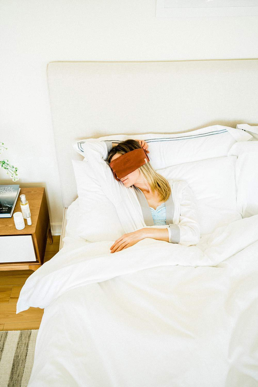 Woman lying in bed with white sheets and eye mask on and a bedside table with Sagely Naturals products.
