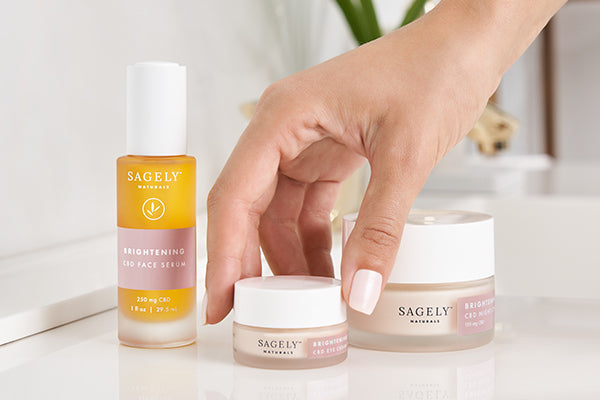 A hand picking up Sagely Naturals Brightening CBD Eye Cream which is sitting on a sink counter next to CBD Serum and CBD Night Cream