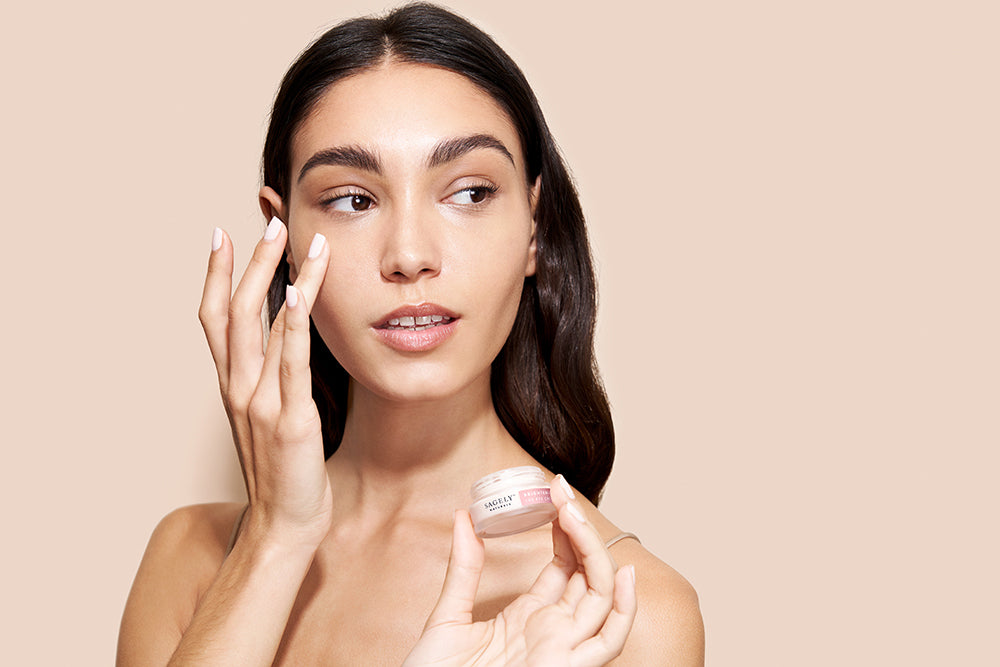 A woman gently applying Sagely Naturals CBD Eye Cream to her skin