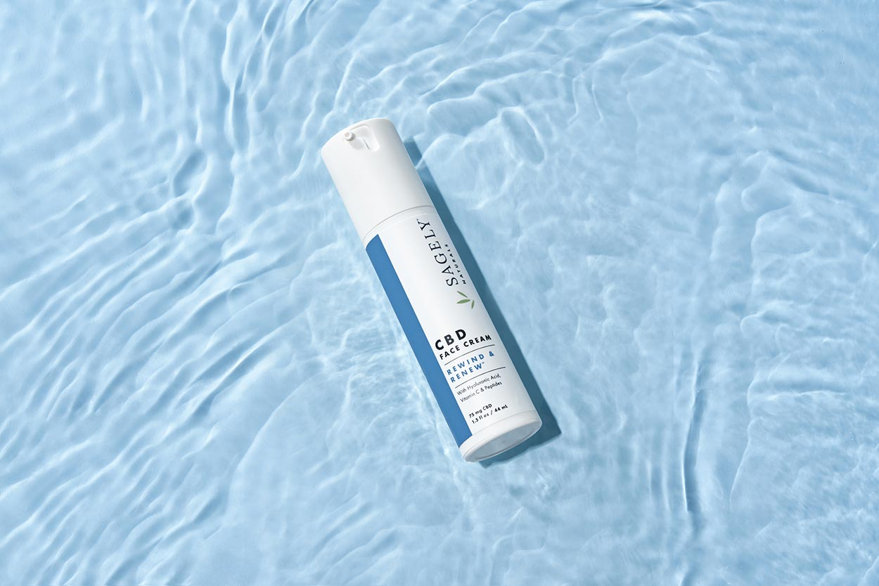 Sagely Natural's new CBD skincare face cream, pictured brightly on light blue water.
