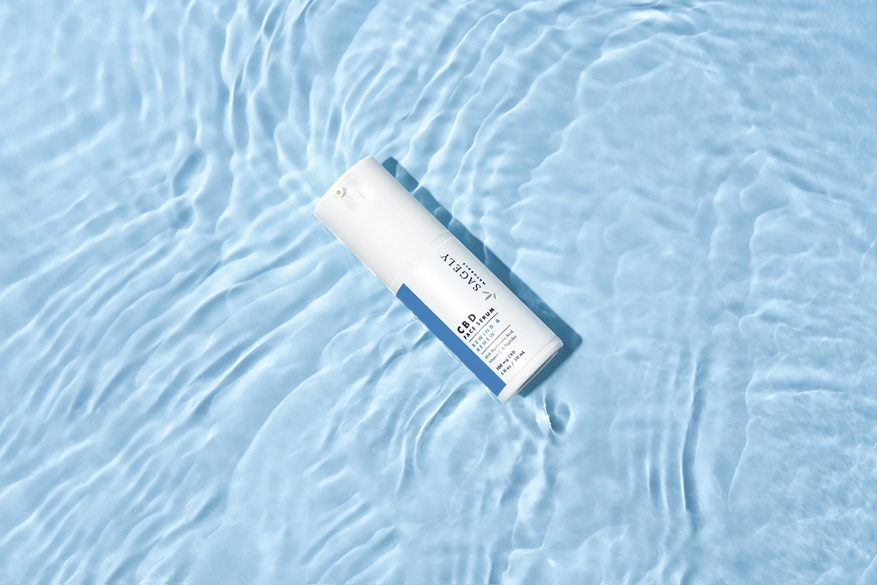 Sagely Natural's new CBD skincare face serum, pictured brightly on light blue water.